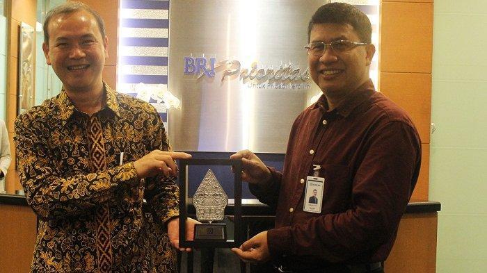 Finance Director BFI Finance Sudjono memegang cinderamata bersama Executive Vice President Consumer Lending Sales and Development Division BRI Handaru Sakti setelah penandatanganan kerja sama pelayanan kredit kendaraan bermotor sampai Rp 1 triliun yang dilakukan di Kantor Pusat BFI Finance, Kota Tangerang Selatan, Banten, Selasa (26/8/2020), Dok. BFI Finance.